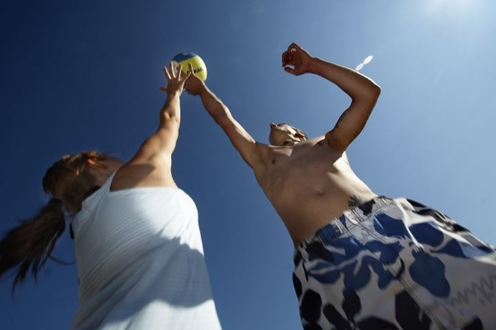 Low angle view of a woman with a man playing beach volleyball, Sweden
