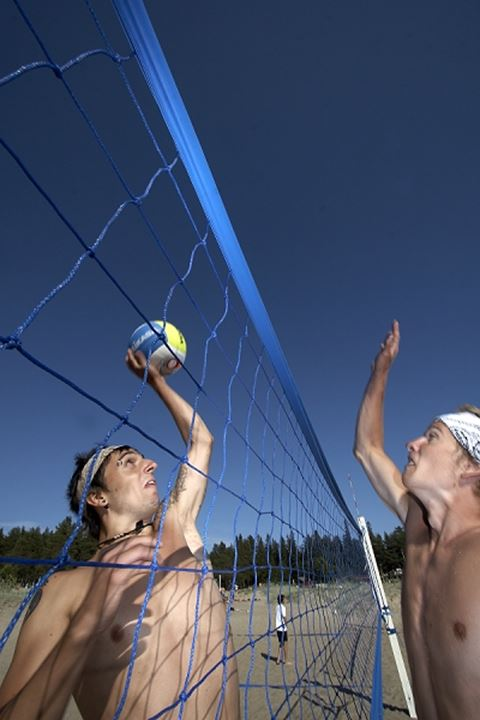 Two young men playing beach volleyball