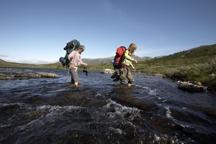 Trackers in Lapland, Sweden crossing a stream