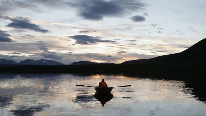 Silhouette of a person rowing boat in a lake, Swedish Lapland, Sweden