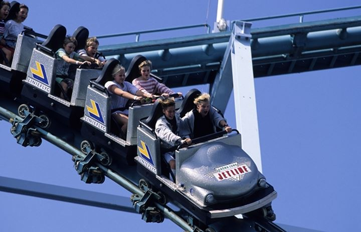 People riding in a roller coaster