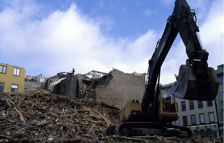 Houses being demolished by a heavy plant machinery