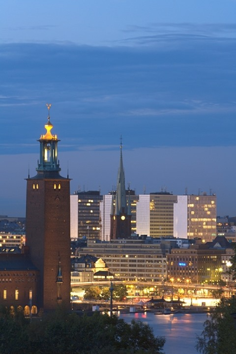 Buildings in a city lit up at dusk, Town Hall, Stockholm, Sweden