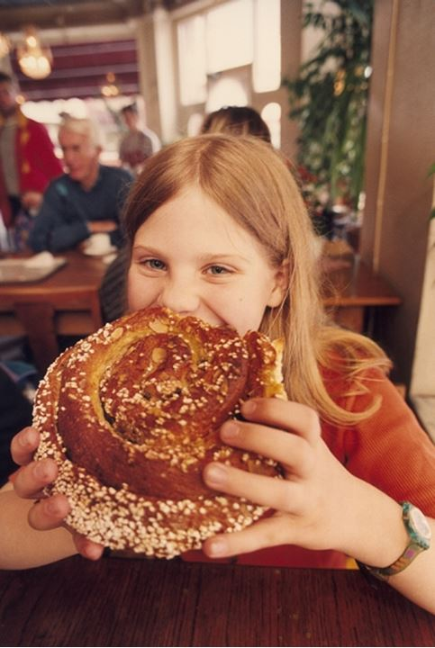 Front view of a girl eating baked bread roll