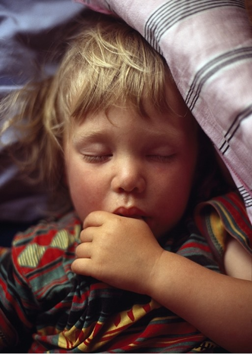 Close-up of a boy sucking his thumb while sleeping