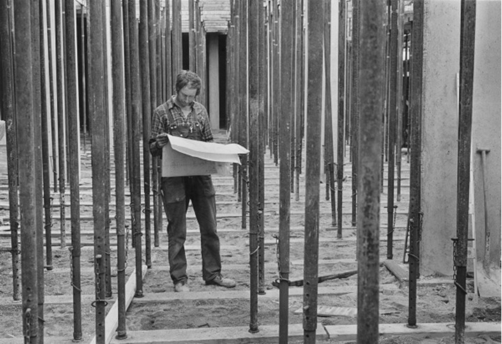 A man reading blue print at construction site