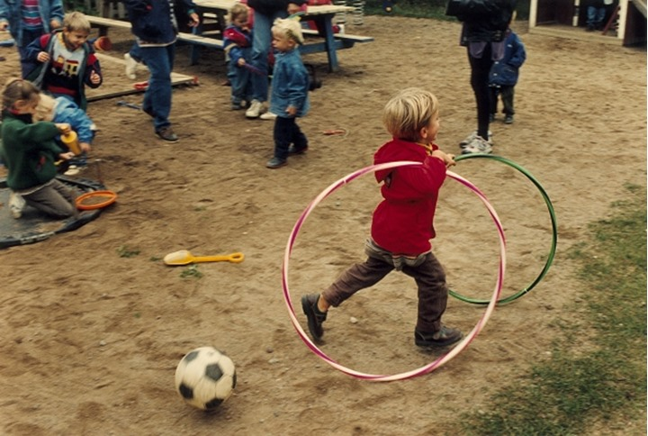 Rear view of a boy running with two plastic hoops in the park