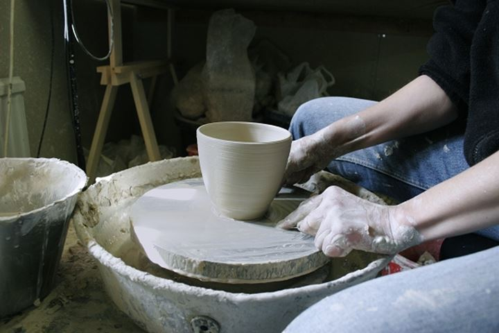Mid section view of a woman making a pottery