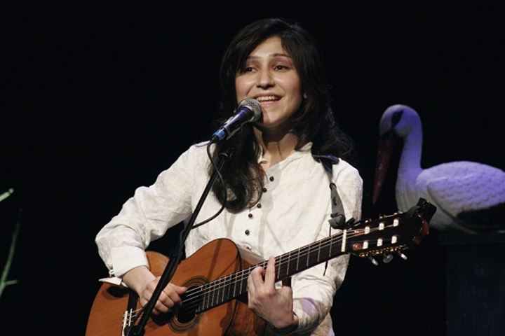 Front view of a woman playing guitar while singing