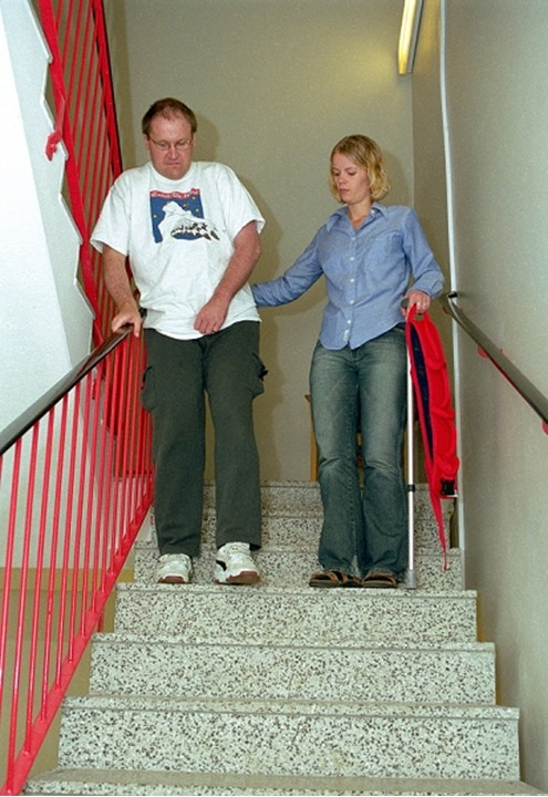Fysiotherapist training a strokepatient to walk in stairs.
