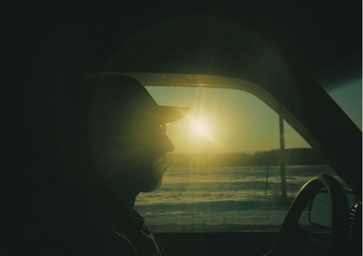 Silhouette of a person driving car at evening, USA