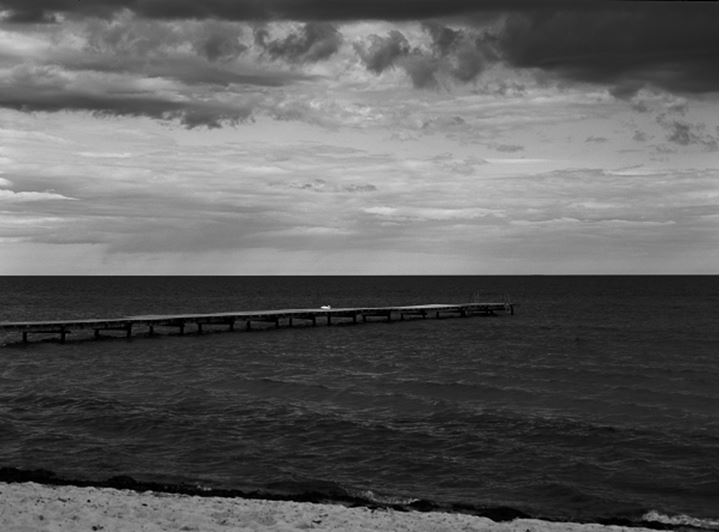 Long wooden dock stretching out in the ocean, Skane, Sweden