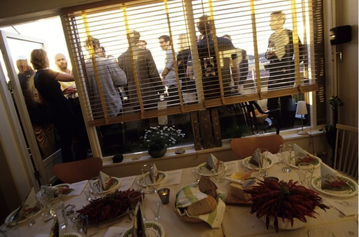 People standing at the door of a room with a dinning table in the foreground
