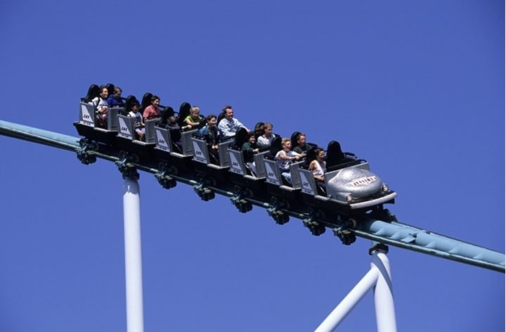 People riding in the roller coaster against blue sky