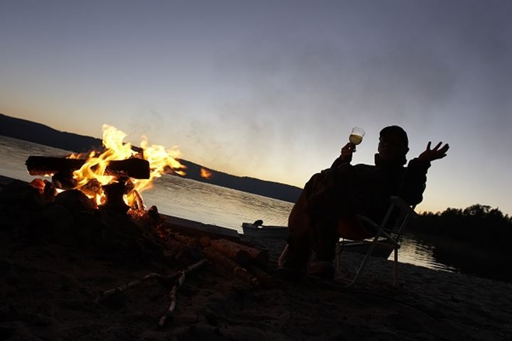 Silhouette of a person drinking beverage whilst sitting by the bonfire