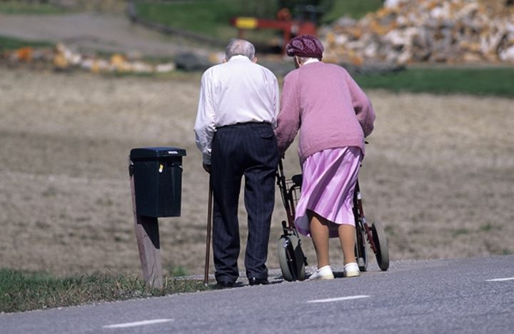 Rear view of a couple walking with wheelchair