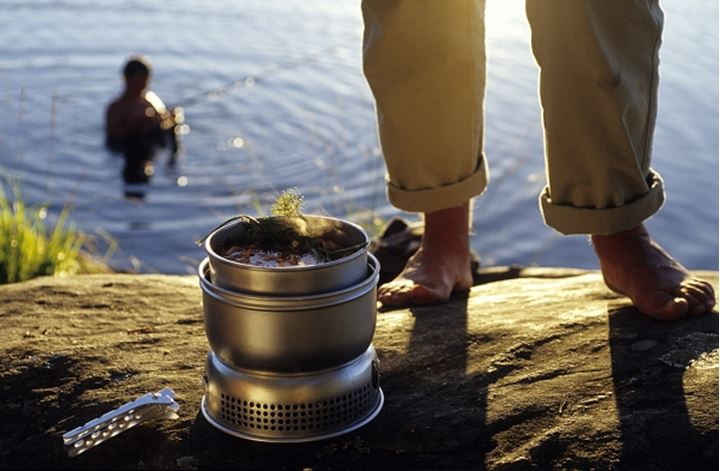 A person cooking by the lake