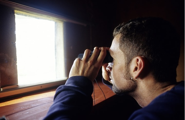 Side profile of a mid adult man looking through a pair of binoculars