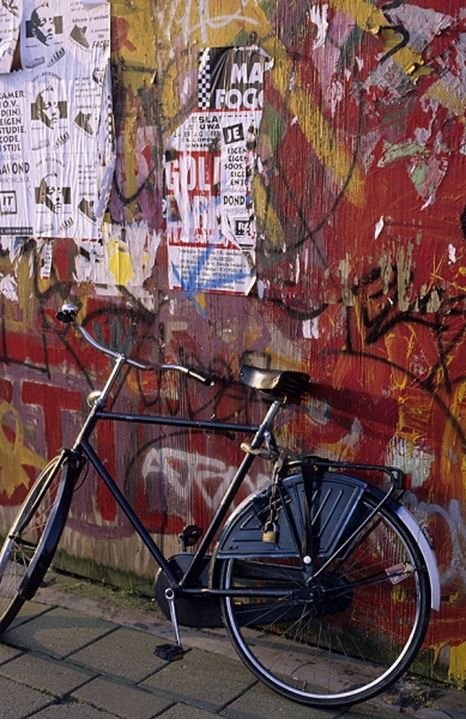 Bicycle leaning against a wall with graffitti in Italy, Europe