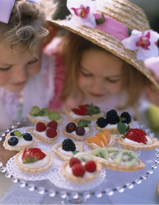 Two girls with plate of toppings