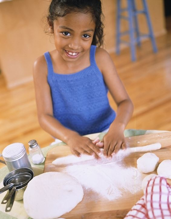 A girl kneading dough and looking at the camera