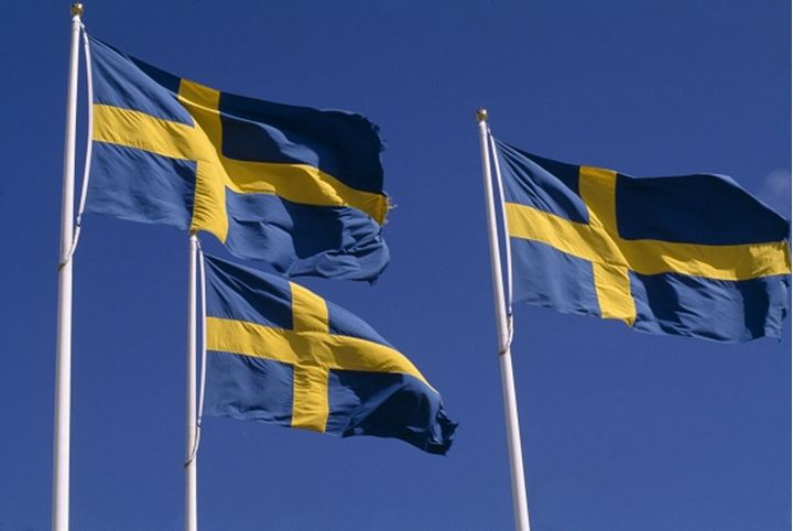 Swedish flags waving against blue sky