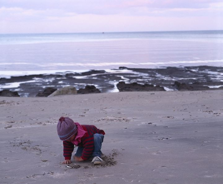 Child playing with sand at a beach