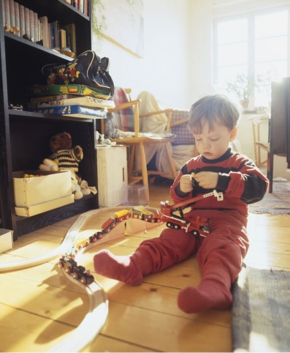 Boy sitting on the floor and playing with a toy train