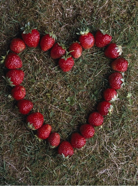 High angle view of strawberries arranged in a heart shape pattern.