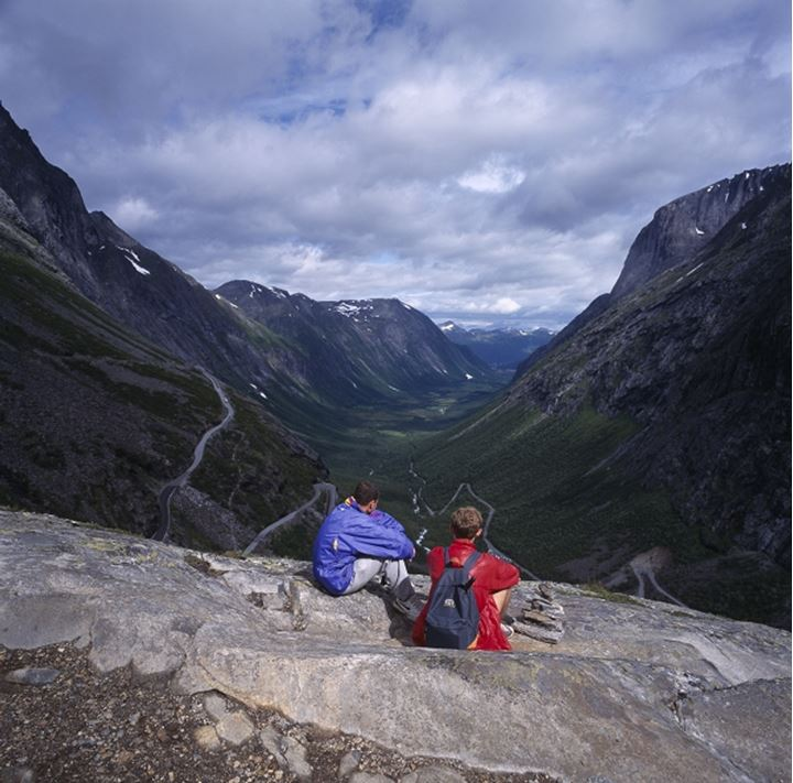 Rear view of two men sitting on a mountain
