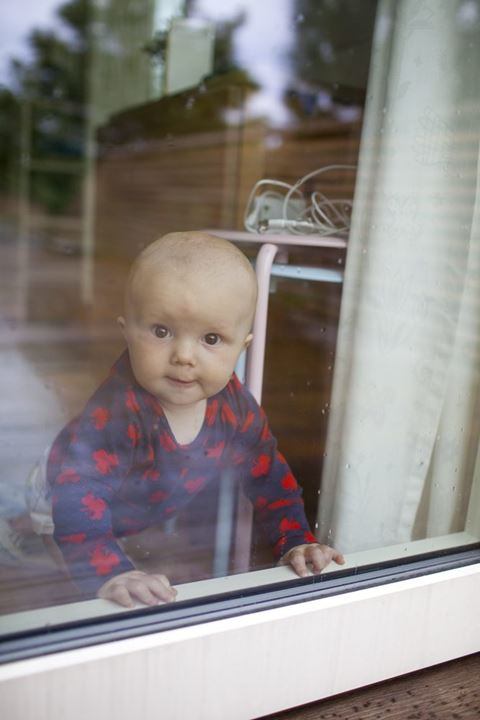 Small baby boy looking out a window, Sweden.