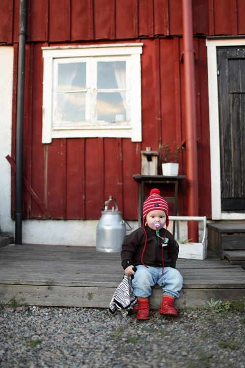Young baby boy sitting on a porch. Sweden.
