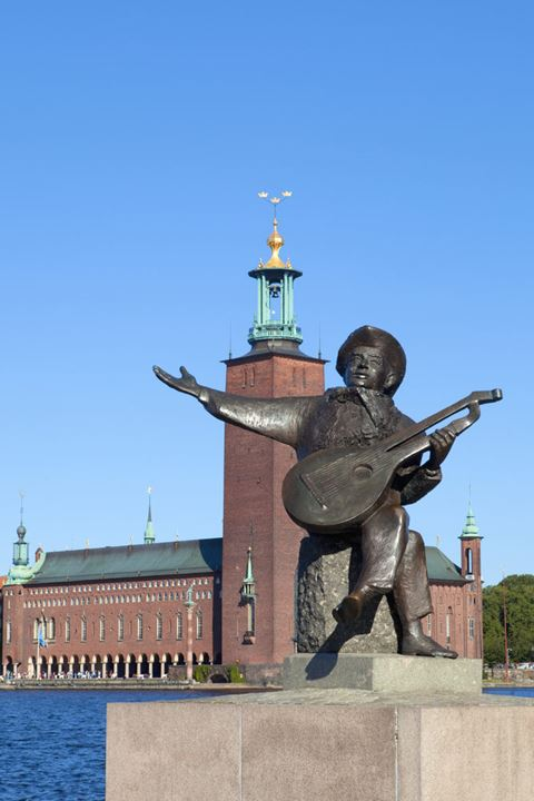 Sweden, Stockholm - The Town Hall ( Stadshuset ) and statue of national musician Evert Taube.