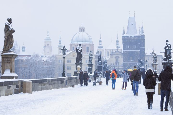 Czech Republic, Prague, Charles Bridge -  people walking during snowfall