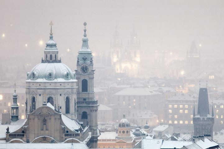 Prague - St. Nicholas church and spires of the Old Town during snowfall