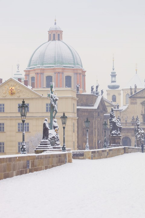 Prague, Charles Bridge - religious art and spires of the old town in winter