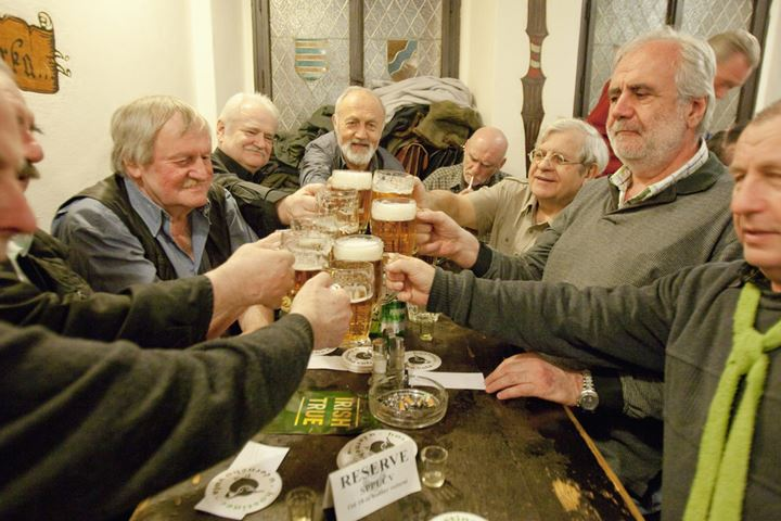 Prague - friends in a traditional Czech pub toasting with beer.