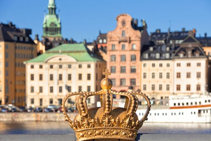 Sweden, Stockholm - The Old Town and Royal Crown on Skeppsholmen Bridge.