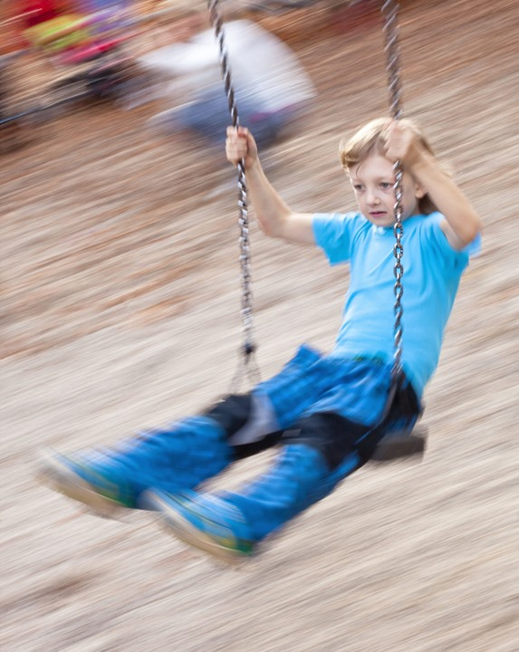 Boy on a Swing in the Playground