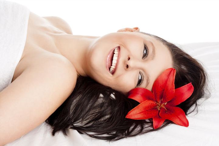 Happy Young Woman Lying on her Back in Spa Relaxing