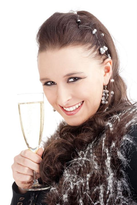 Young Woman Holding a Glass of Champagne, Smiling - Isolated on Wite.