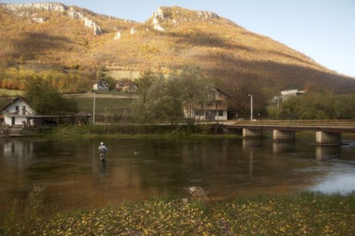 Autum at river Pliva and a flyfiherman is fishinga at the bridge. Its a soft photo.