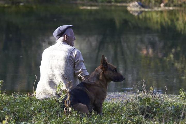 A shepherd with his dog resting at the riverbank. Bosnia.