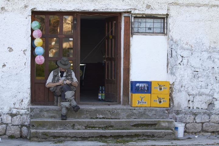 A flyfisherman sitting in front of a shop in Bosnia.