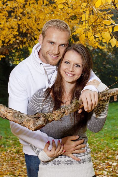 portrait of a happy young couple in the park, embracing, smiling.