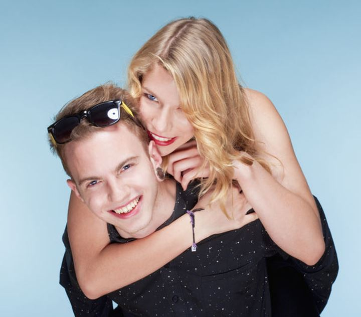 happy teenage couple piggybacking, smiling - isolated on blue.