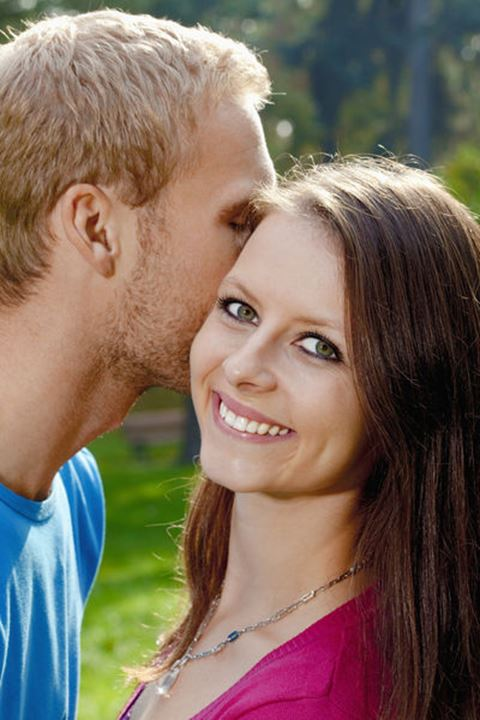 Young Girl Smiling as her Boyfriend Whispers in her Ear.