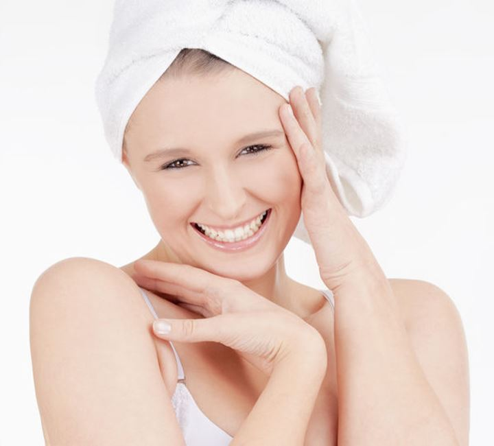Beautiful Young Woman with Towel on her Head Smiling - Isolated on White