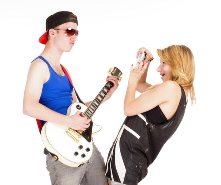 Teenage Couple - Girl Taking Pictures of her Boyfriend with Guitar - Isolated on White
