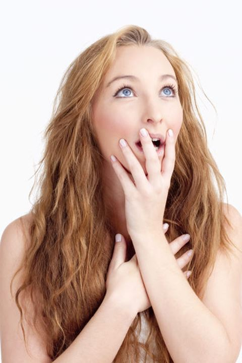 Young Woman with Long Brown Hair Looking Surprised, Hands on her Mouth